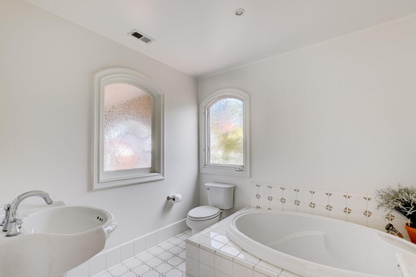 The ensuite bathroom includes a soaking tub