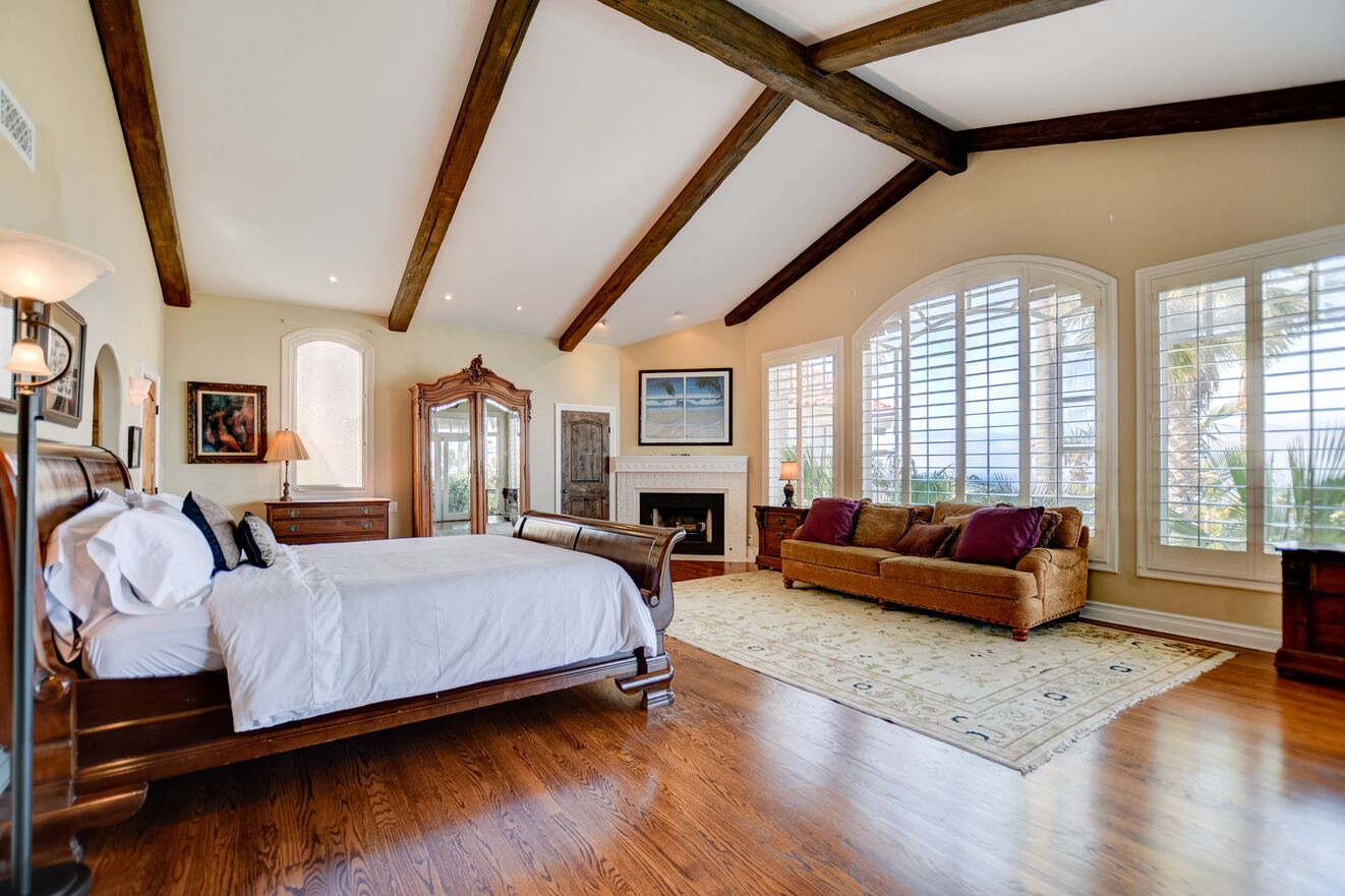 The first-floor master suite features a decadent open rafter ceiling, fireplace, and King size bed with luxury bedding