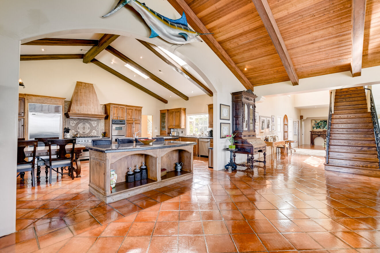 The large open floor plan capitalizes on high beam ceilings, light, and Mediterranean design throughout