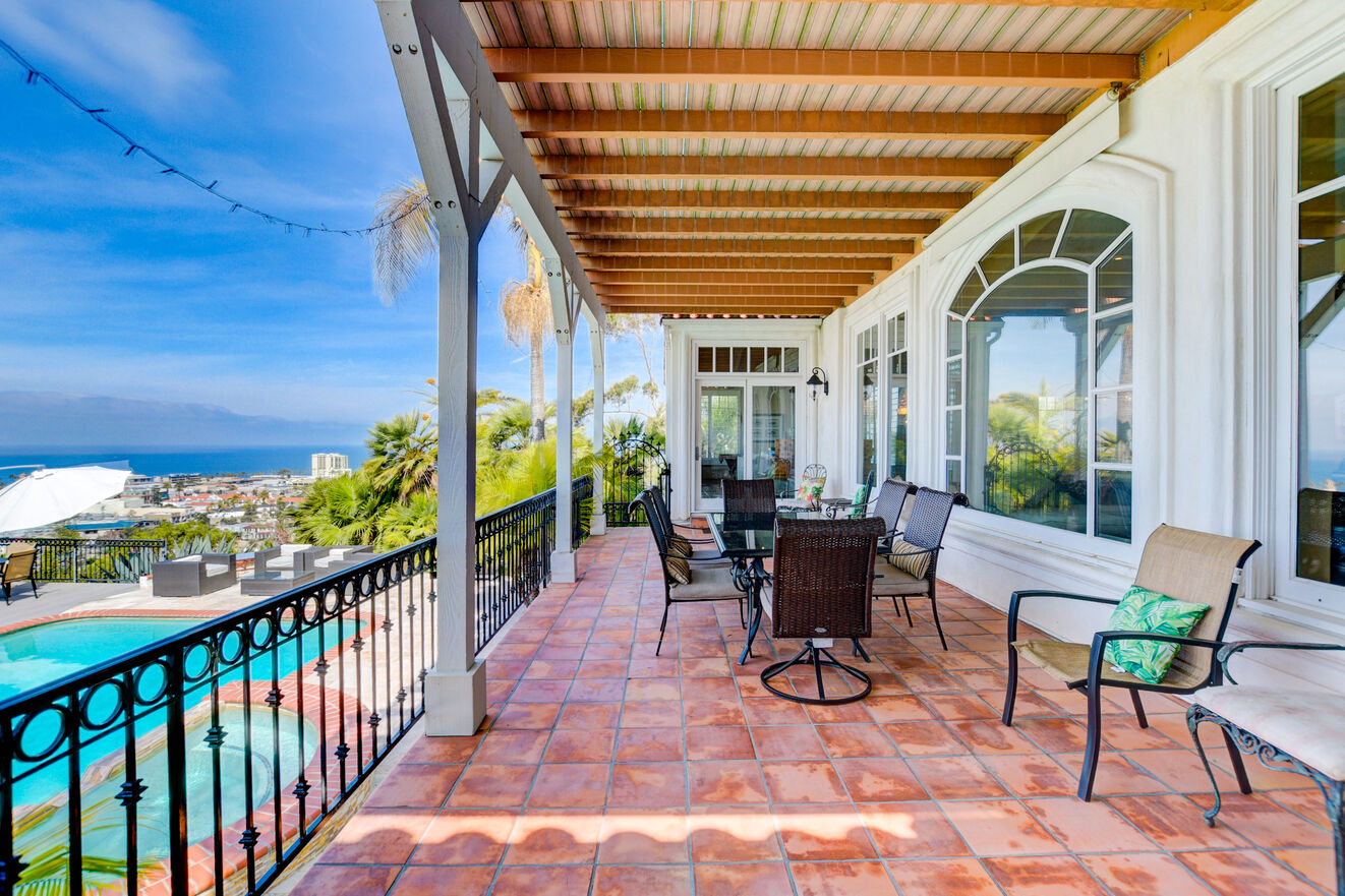 First floor balcony overlooks the pool and the Pacific Ocean with dining and lounge furniture with entrance from the family room