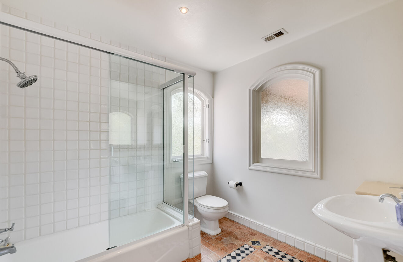 The ensuite bathroom has a tub and shower combo