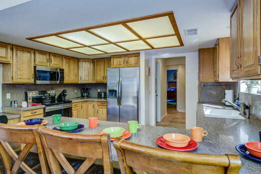Fully Equipped Kitchen with Stainless Steel Appliances and Bar Seating