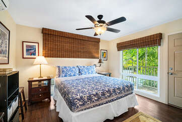Large bed, ceiling fan, and sliding doors to the balcony