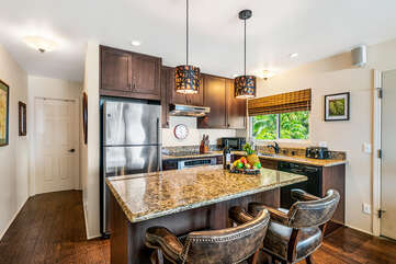 Kitchen island, counter stools, refrigerator, microwave and toaster