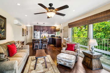 Living room with sofas, ceiling fan, and the kitchen