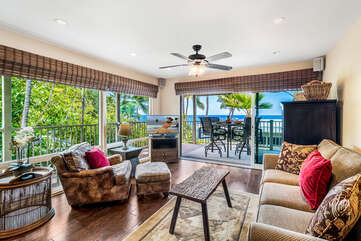Living room with views of the ocean, sofa, armchair, ceiling fan, and smart TV