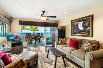 Sofa, armchair, ceiling fan, smart TV, and sliding doors to the oceanfront lanai