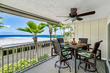 Covered lanai with table, chairs, and ceiling fan in our ocean front condo Kauai