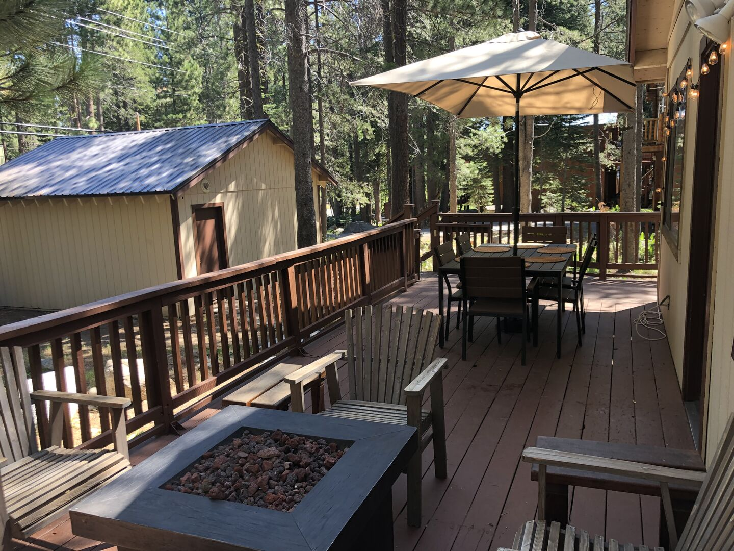 Large Deck Features a Fire Pit and Table with Umbrella