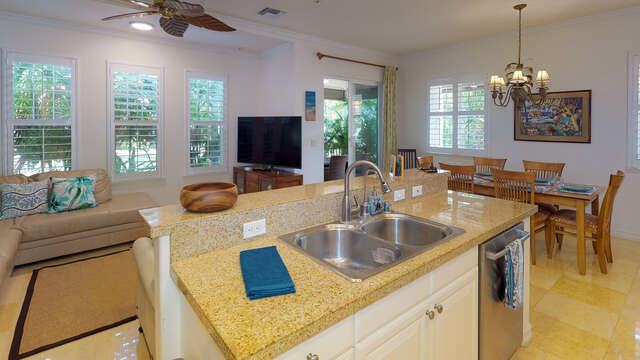 Kitchen island with nearby televise, couches and table