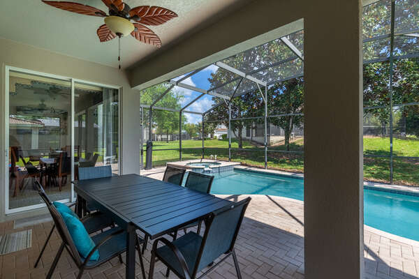 Dine al fresco underneath the covered lanai with seating for 6 and two ceiling fans for those hot summer days