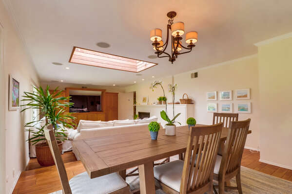 Dining Room with plenty of houseplants, wooden furniture, and a view into the living area.