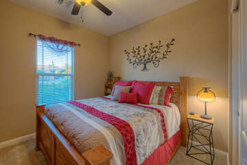 The home's second bedroom has a king bed, ceiling fan and television