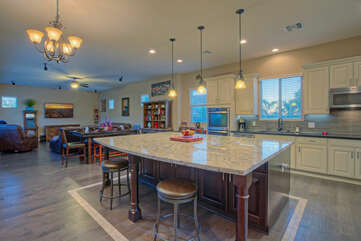 Open floor plan includes expansive and modern kitchen with island seating and pendant lighting