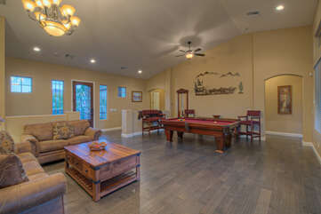 Spacious and elegant game room at back of the home has a sleeper sofa and grand pool table