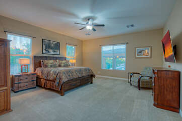 Large primary suite features a king bed, television and ceiling fan