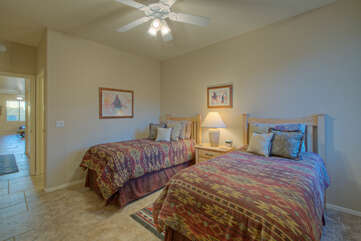 Second bedroom has two twin beds and a ceiling fan