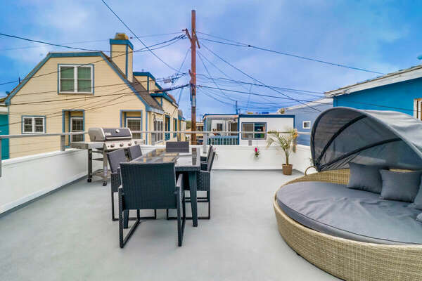 Roof Deck with large covered couch, tale with chairs, and grill.