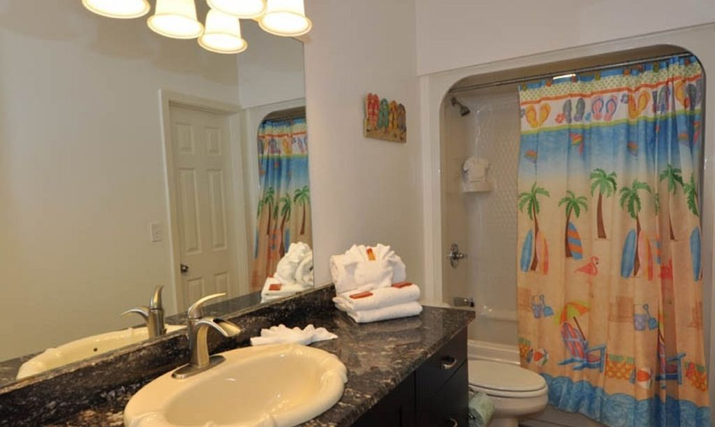 Bathroom with Shower-Tub Combo, Sink, and Mirror.
