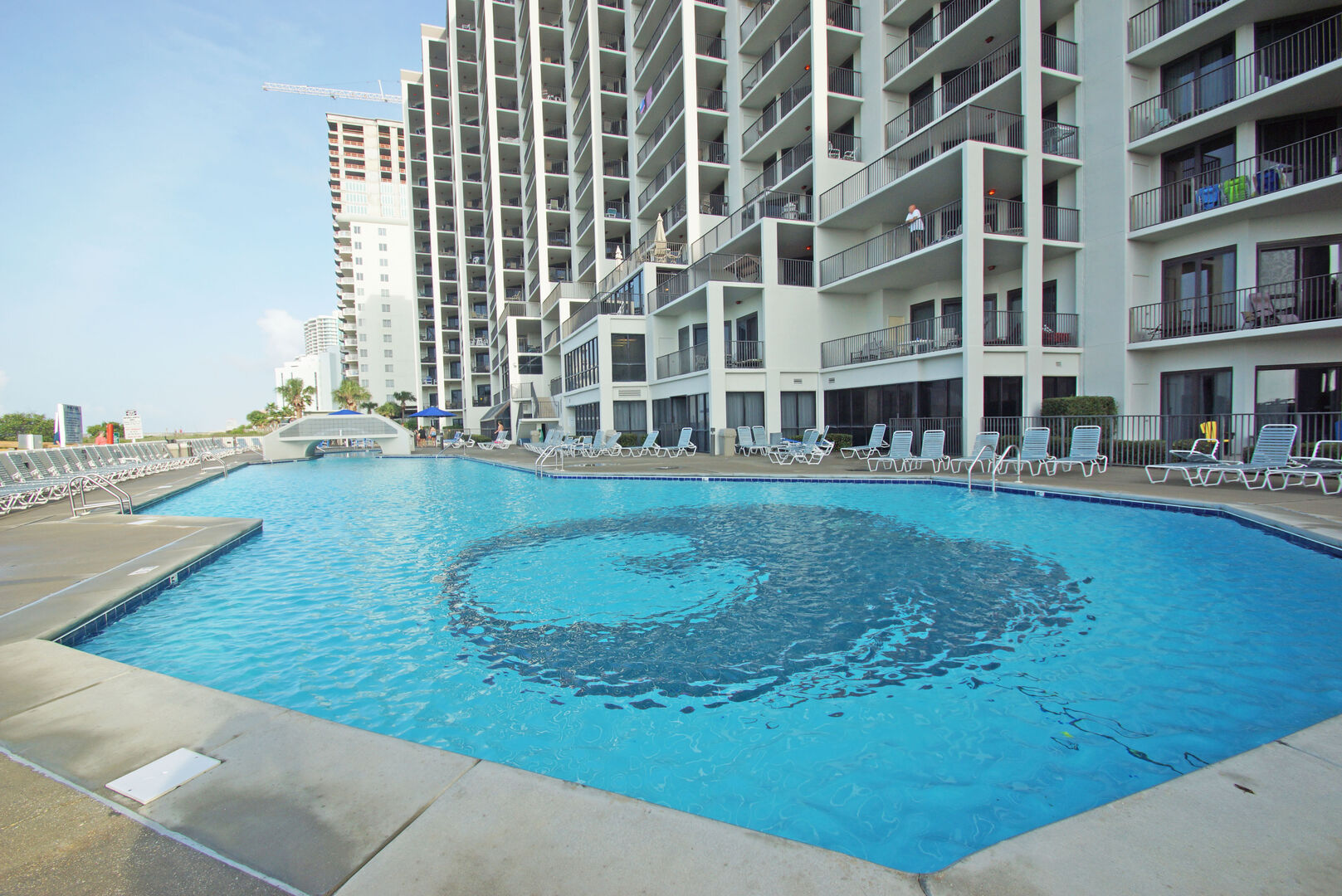 Picture of the Community Pool Surrounded by Lounge Chairs.