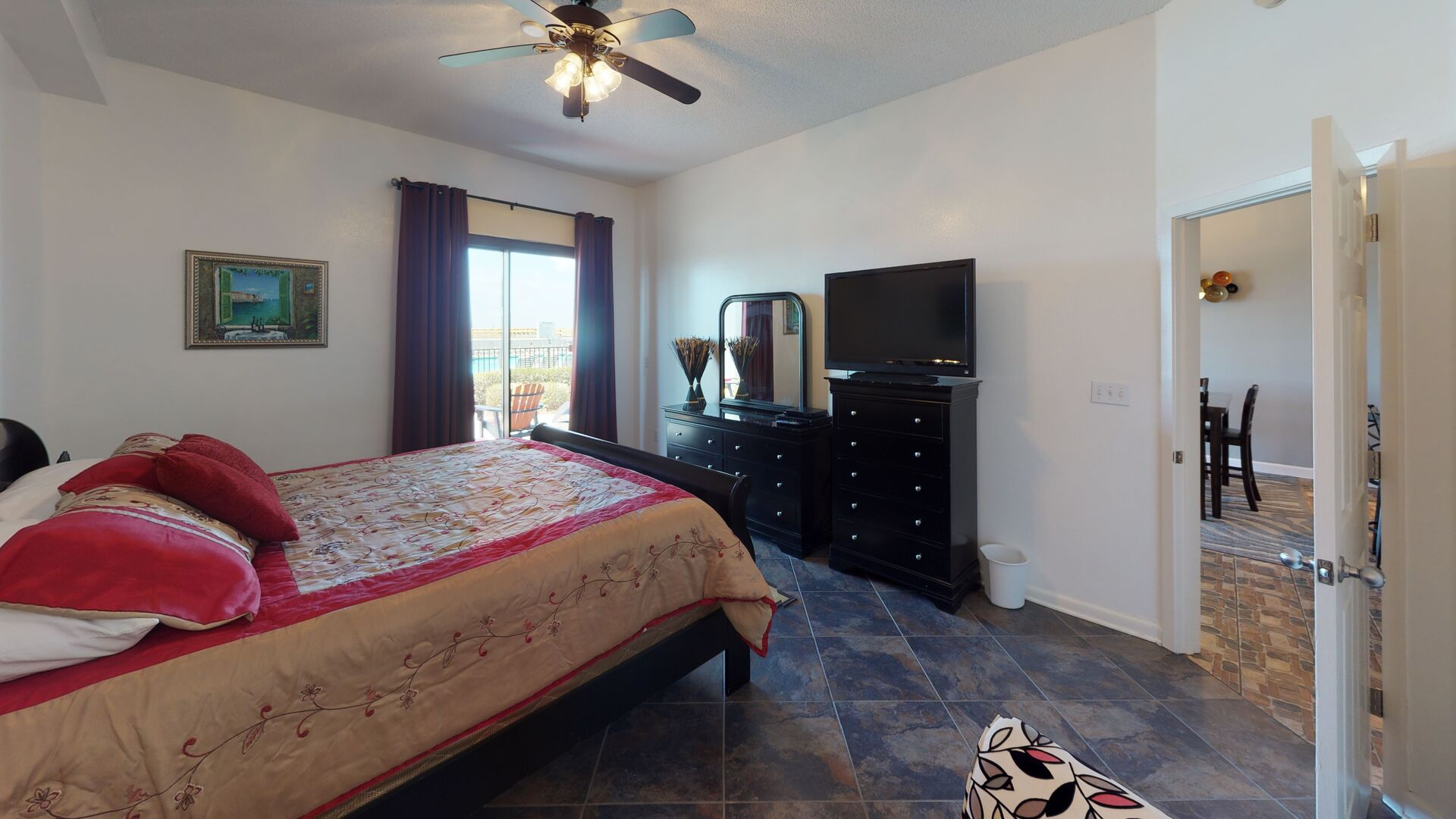 Large Bed, Dresser, TV, Drawer Chest with Mirror, and Ceiling Fan.