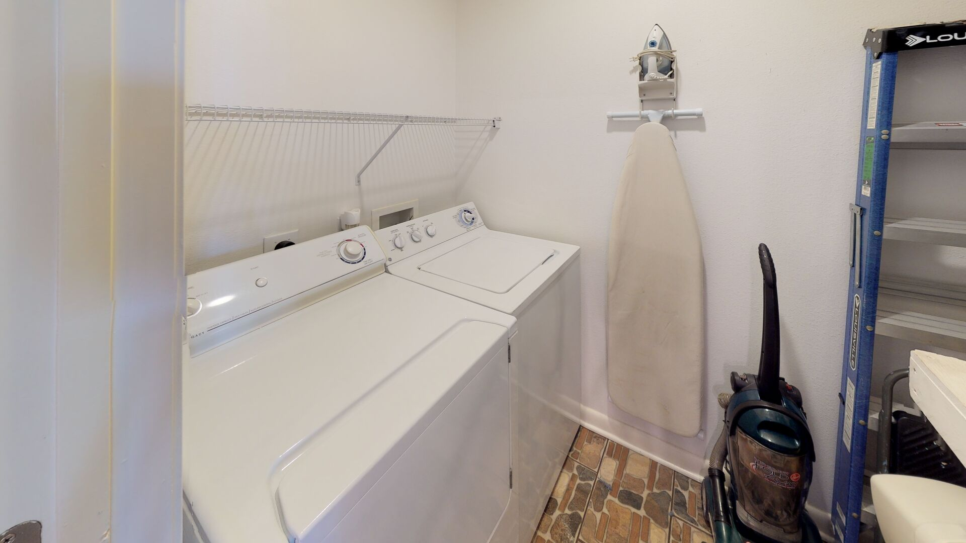 Laundry Room with Washer, Dryer, Iron, and Ironing Board.