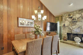 Open floor dining and living room with a flat screen TV and a fireplace!