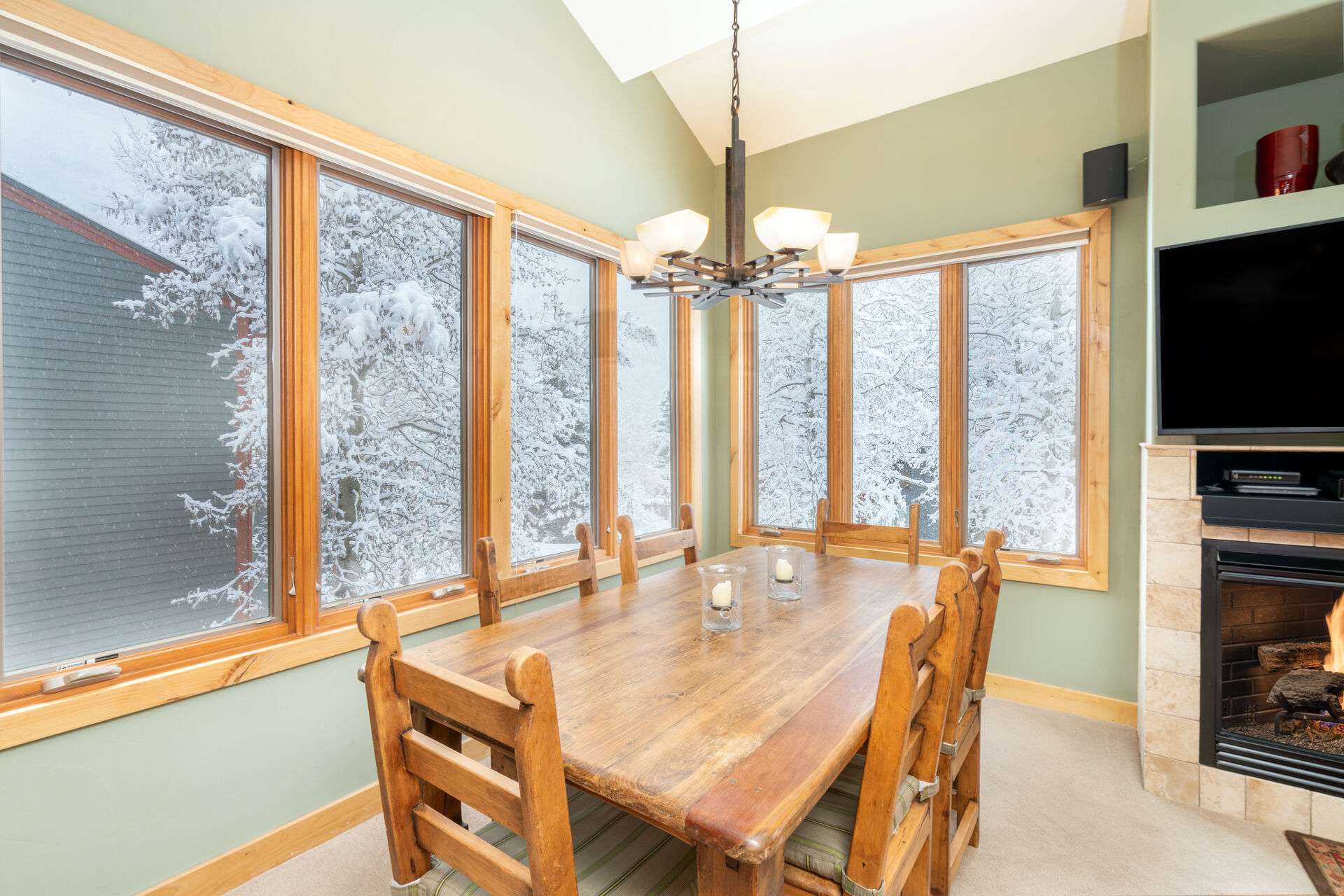 The dining room of this 2 bedroom condo in Telluride with seating for 6 and wrap-around windows.