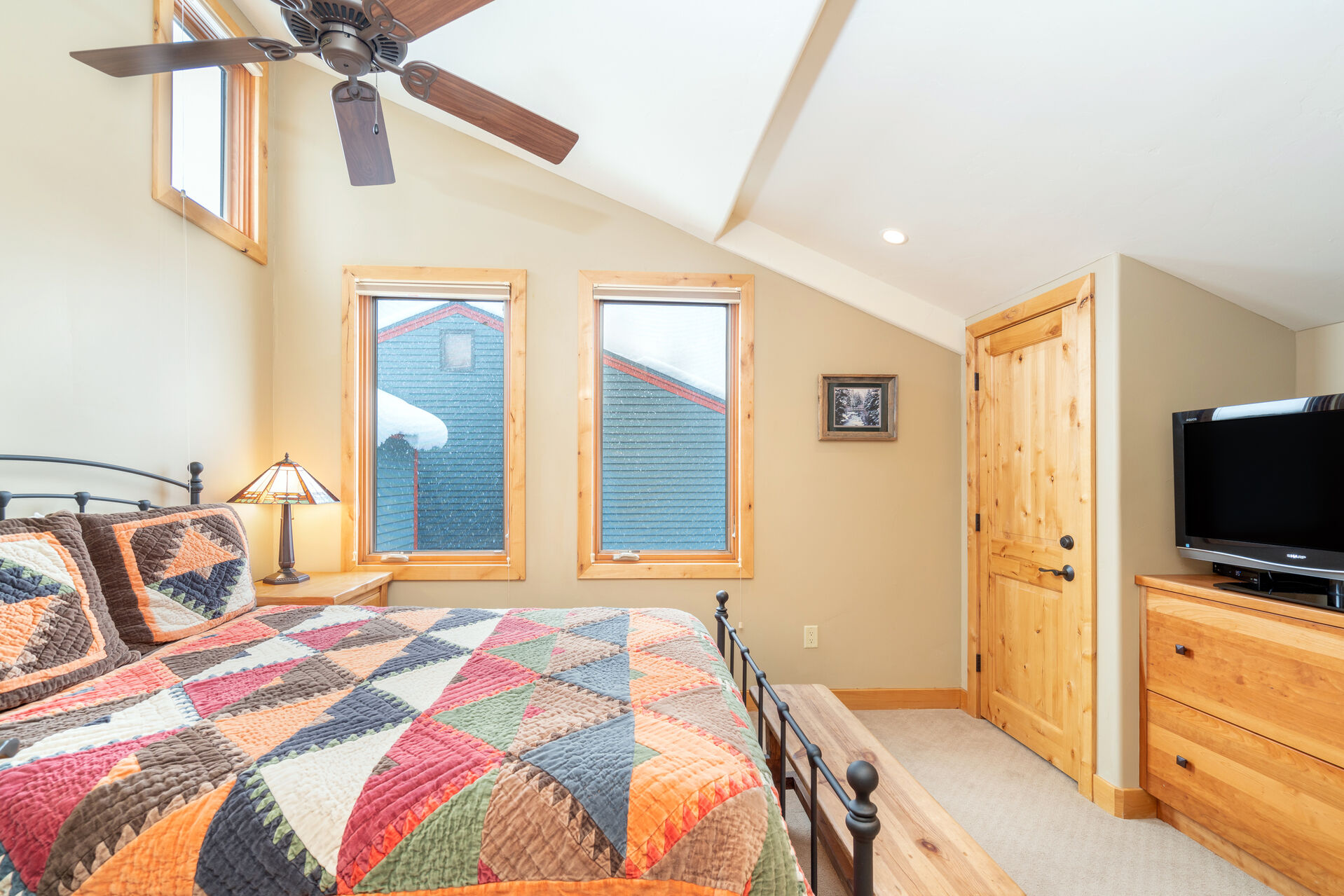 Bedroom of this 2 bedroom condo in Telluride with ceiling fan, dresser, and TV around a large bed.