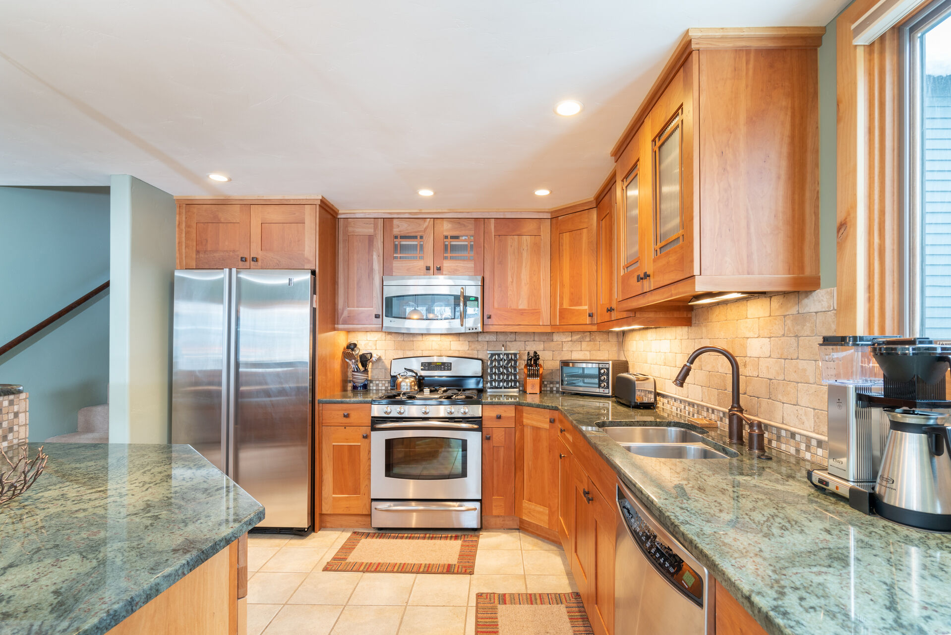 Stainless steel oven, microwave, and fridge of the kitchen.