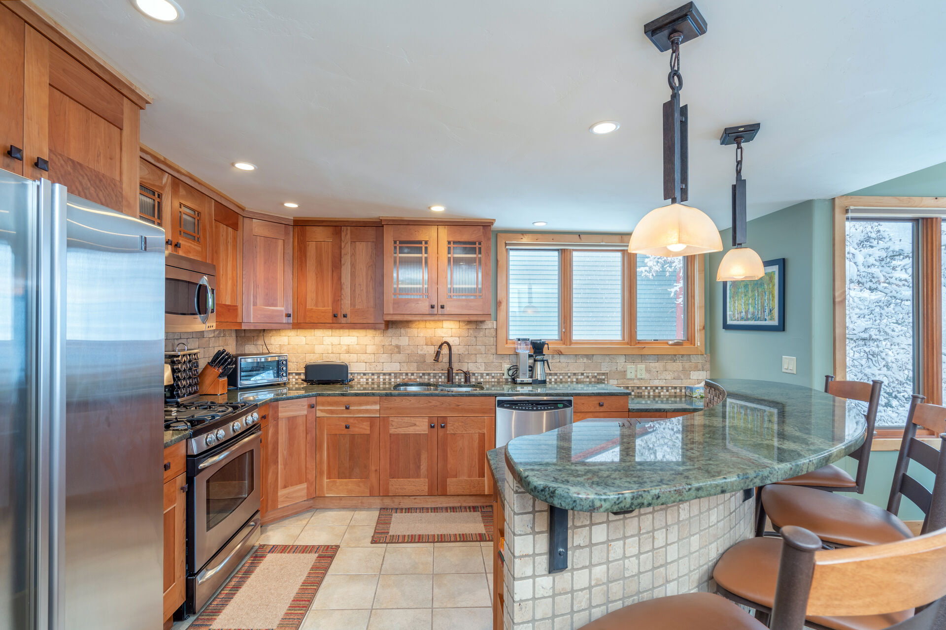 The fully equipped kitchen of this 2 bedroom condo in Telluride, with breakfast bar and stainless steel appliances.