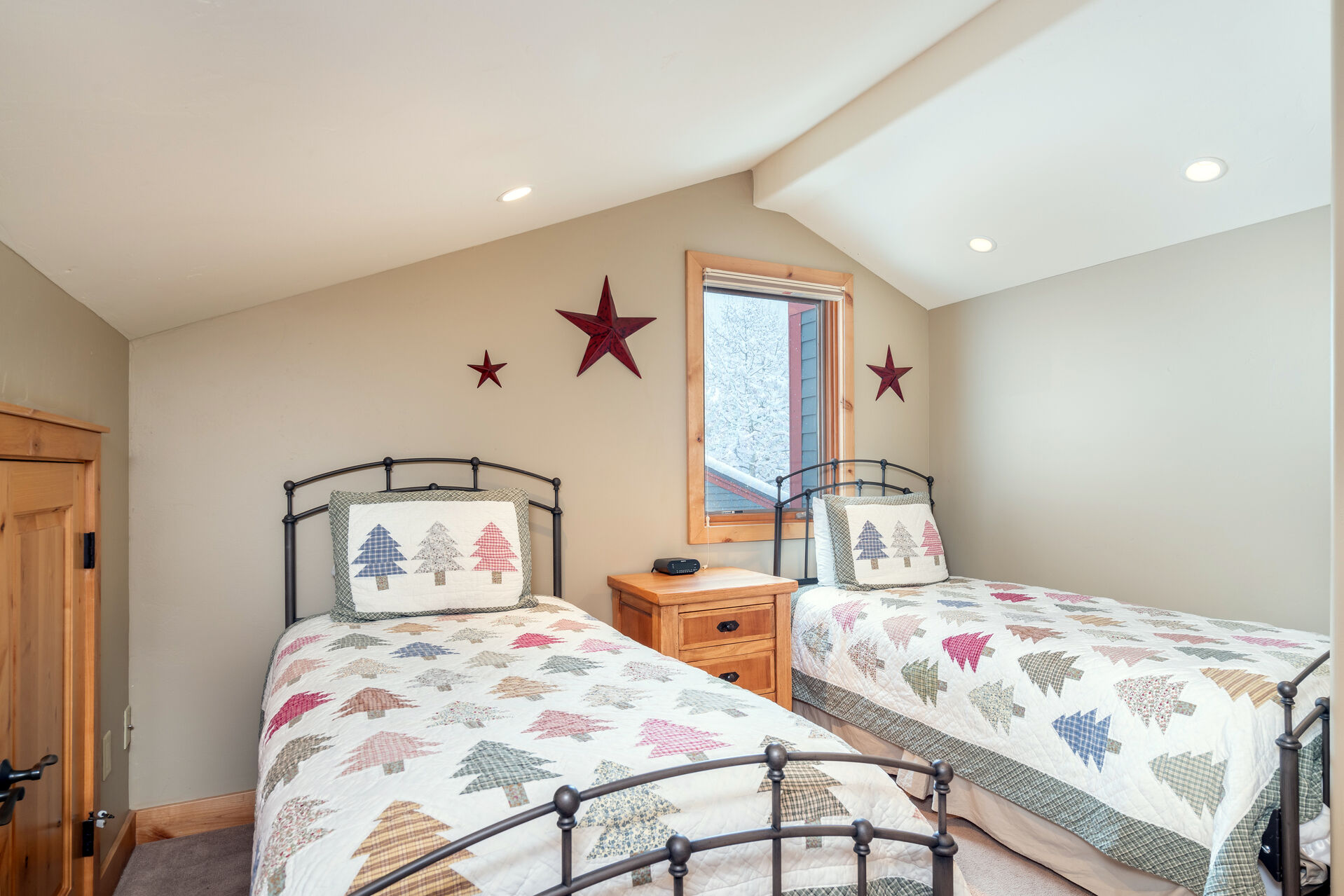 Twin beds with a nightstand in between in the second bathroom.