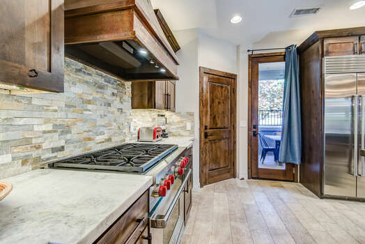 Gourmet Kitchen with Stainless Steel Appliances, including a Wolf 6-Burner Gas Range and Front Patio Access