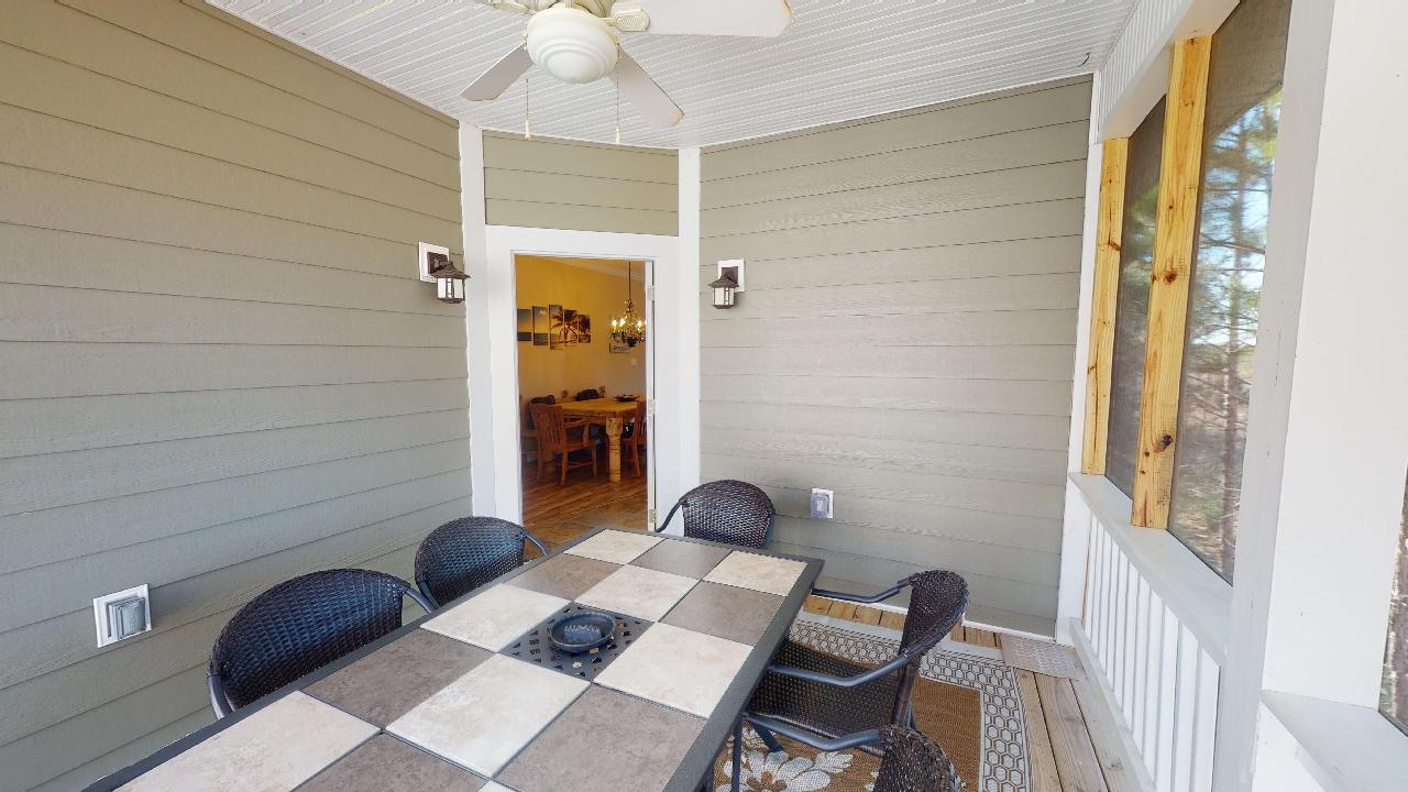 Screened-In Porch Includes a Large Table and Chairs.