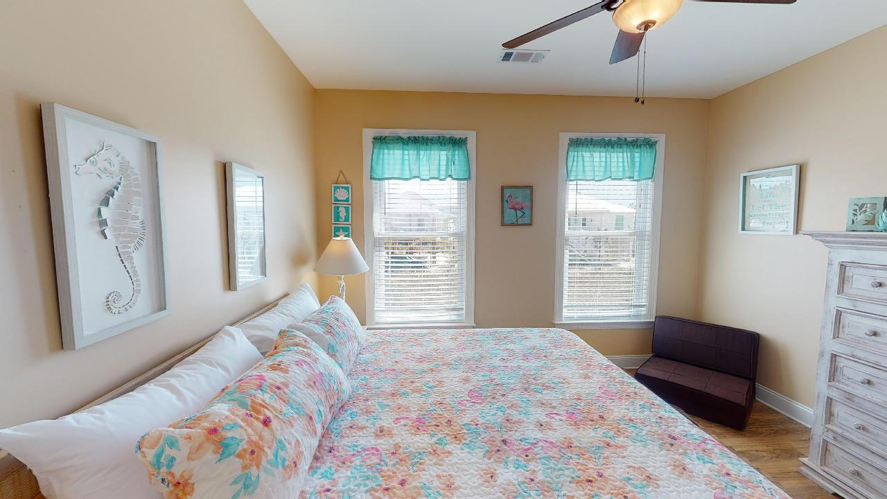 Image of Bed and Two Large Windows in Bedroom.