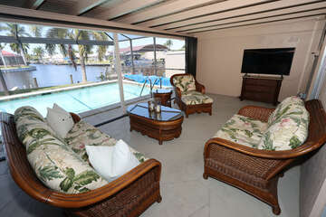 Lanai seating area with flat screen TV, pool and view