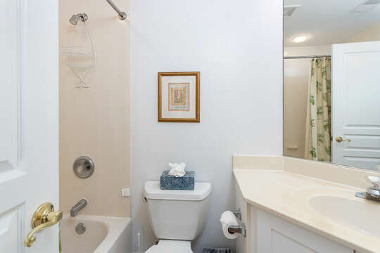 Bathroom with Tub and Shower Unit, Toilet, Mirror, and Cabinet Sink.
