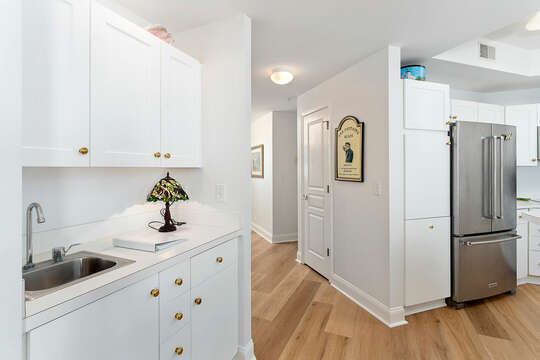 Wall Cabinets with Sink, Pantry Cabinet, Refrigerator, and the Hallway.