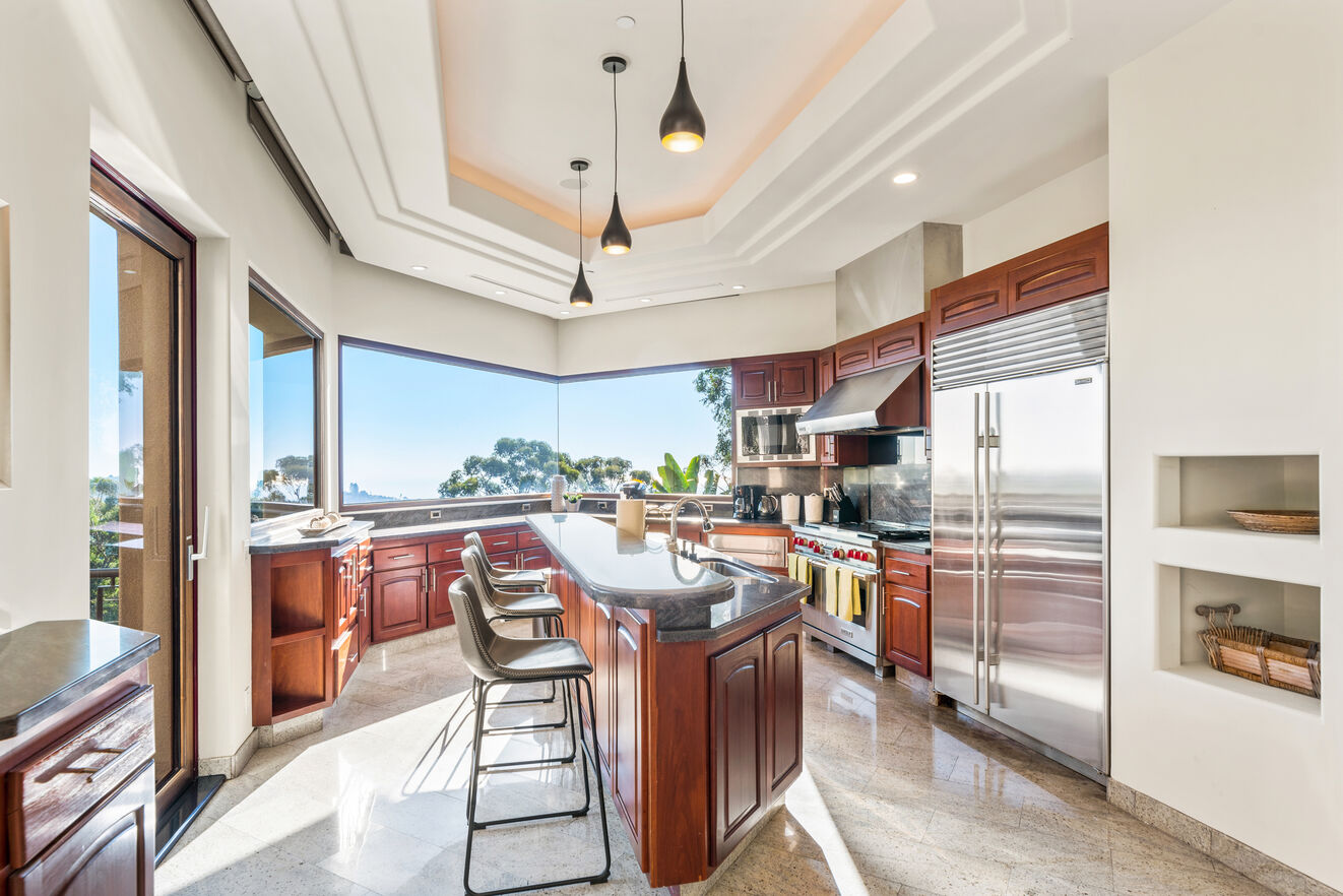 Large kitchen with stainless steel appliances and island seating