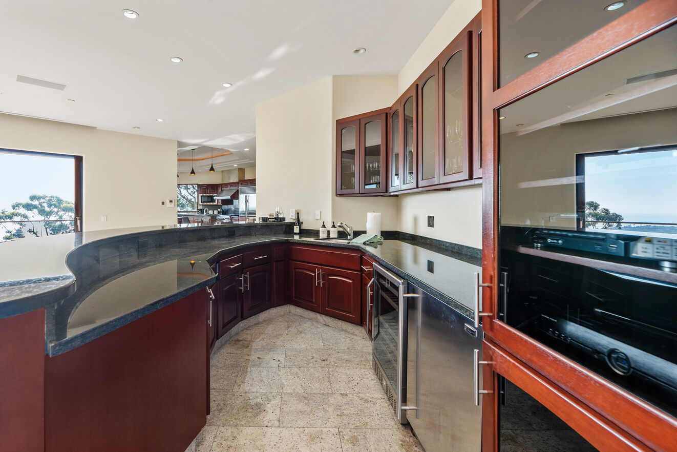 Mid level bar area with wine cooler, refrigerator, bar sink and more