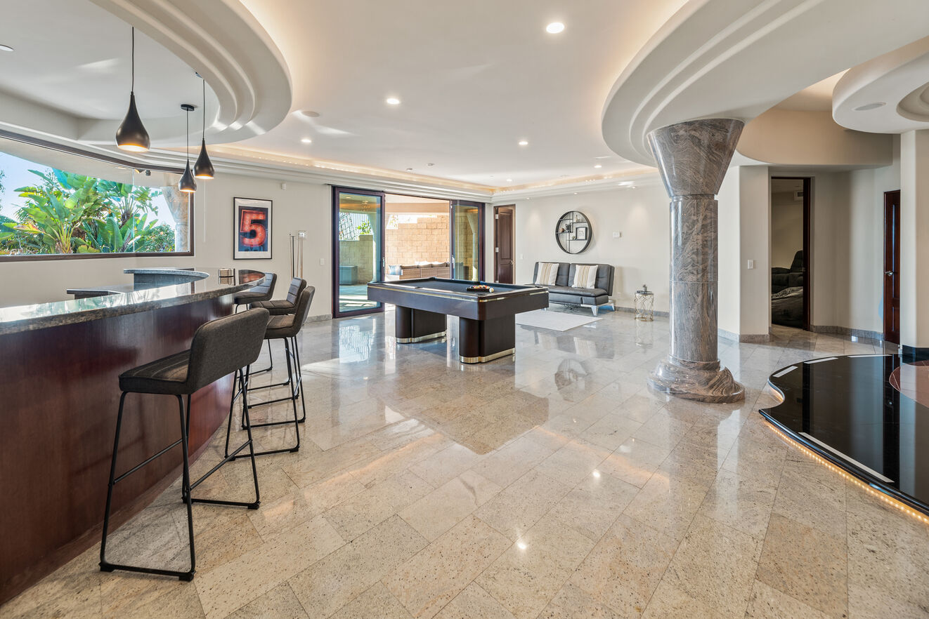 Downstairs living area with full bar, pool table, pool/patio access and 2 leather futons