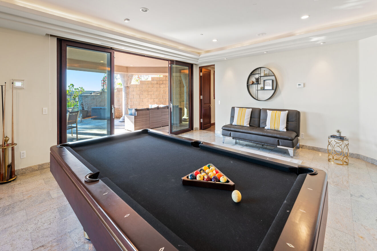 Pool table and bar opens up to back yard with pool and outdoor kitchen.
