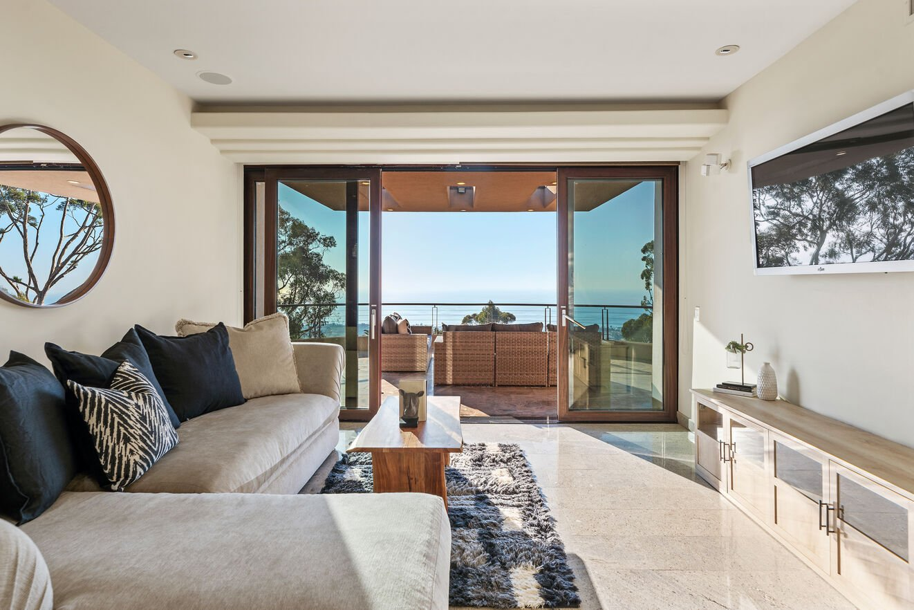 Upstairs sitting area with flat screen tv and sliding doors opening to balcony with outdoor sofa seating and the best views of the house.