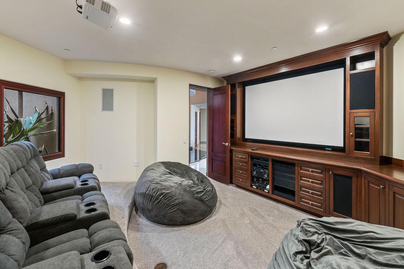 Theater room downstairs with 2 bean bags and 7 reclining theater seats, theater screen with projector and Fire Stick TV streaming access to all media apps (subscriptions required)
