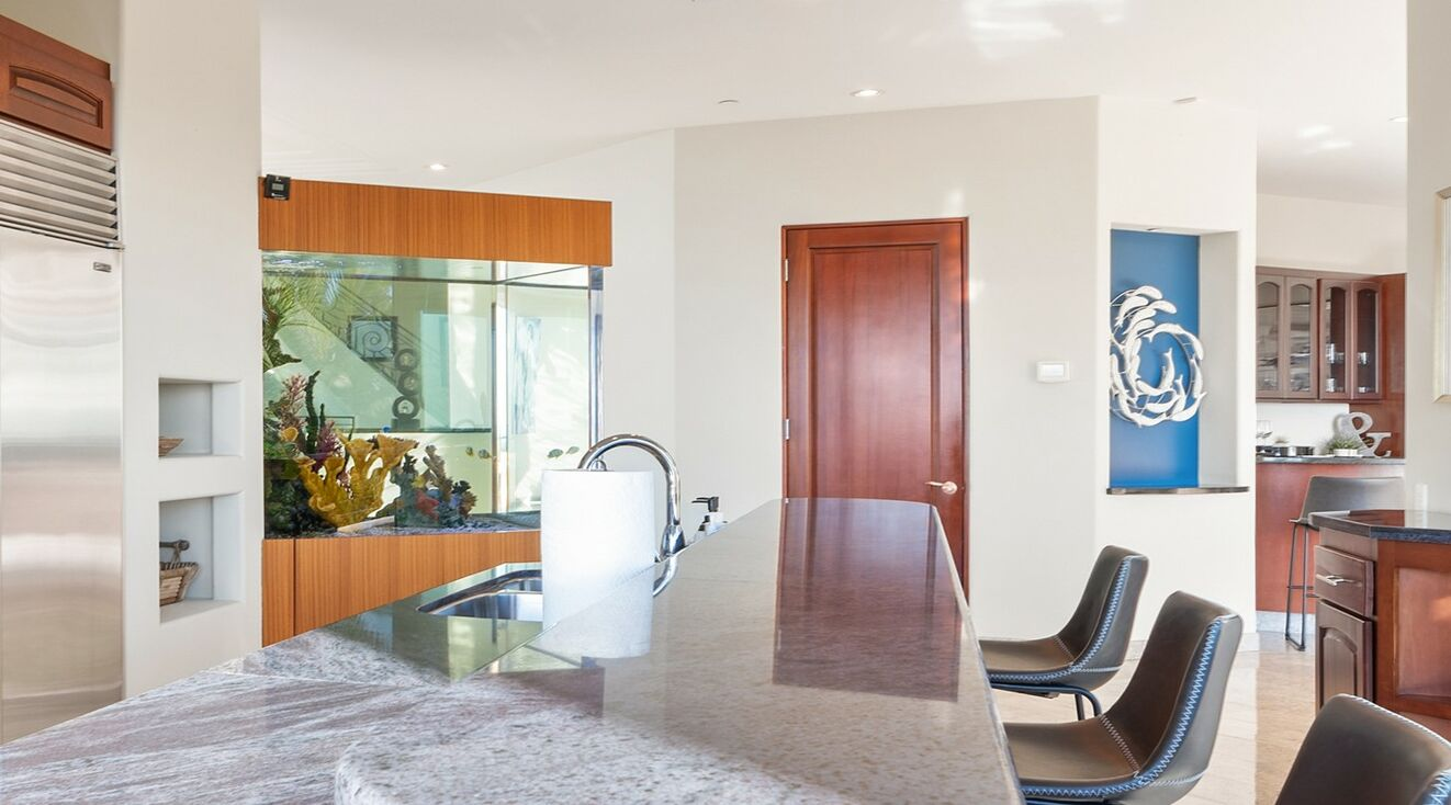 From the kitchen looking through a magnificent acquarium, walk in pantry and mid level full bar area