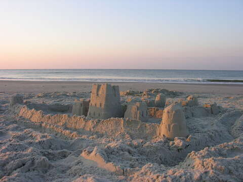 Sandcastles being built on the beach near this home.