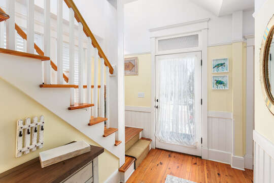 Entryway with stairs leading to upper floor, and bench on the side of them.