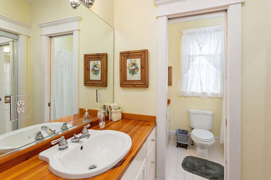 Bathroom with vanity sink and a separate room for the toilet and shower.
