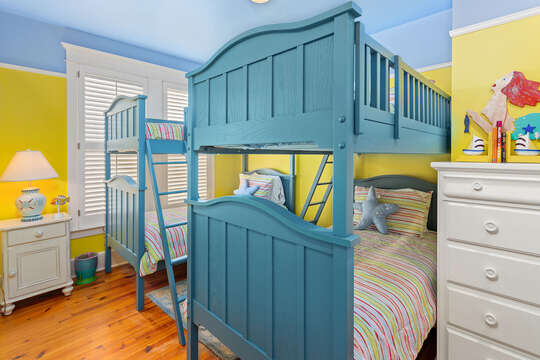 Children's room with twin bunk-beds, dressers, and brightly painted walls.