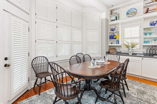 Dining area with table and plenty of chairs, in front of some shelving and counter-tops.